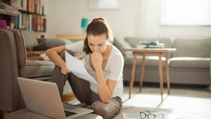 Photo of a young woman sitting on the floor and working on laptop
