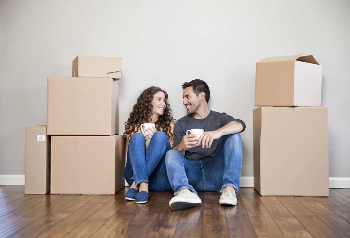 Young couple moving boxes. Taking a coffee break.