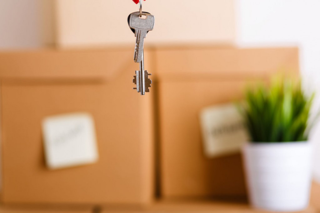 42889839 - female hand holding keys over pile of brown cardboard boxes with house or office goods background. moving to new place of living concept.
